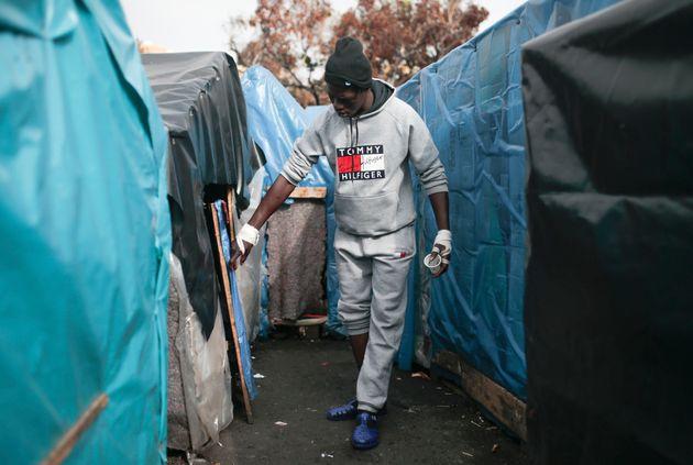 Un migrant marche entre les tentes en plastique du camp de Oulad