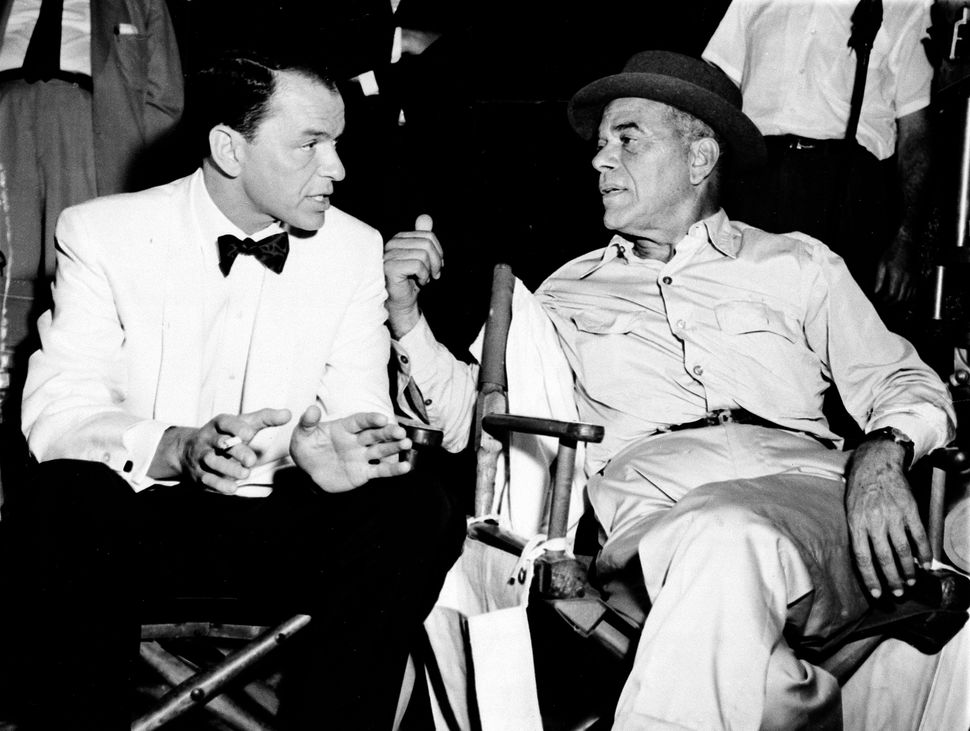 Frank Capra, right, talks with Frank Sinatra on a movie set in Hollywood on Dec. 12, 1958.