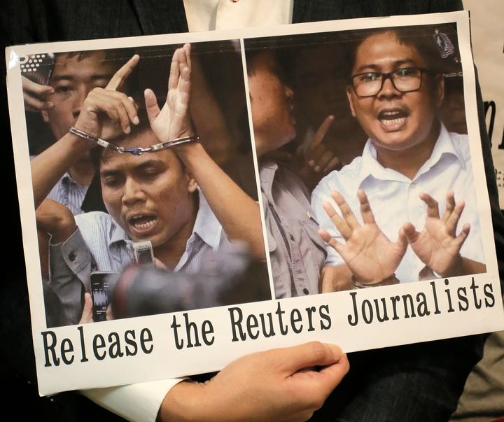 A protester holds a placard outside the Myanmar consulate in Hong Kong after a Myanmar court sentenced two Reuters journalist