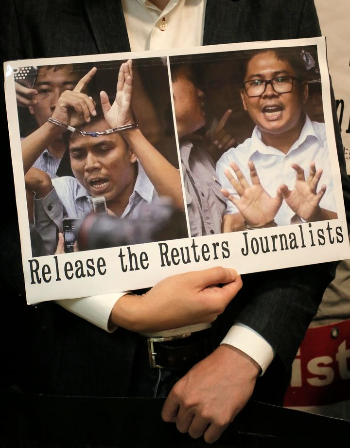 A protester holds a placard outside the Myanmar consulate in Hong Kong after a Myanmar court sentenced two Reuters journalists to seven years in prison.