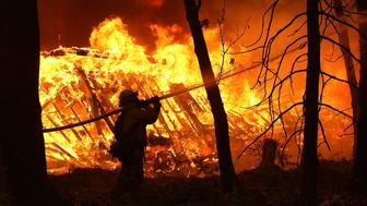 MAGALIA, CA - NOVEMBER 09:  A Cal Fire firefighter sprays water on a home next to a burning home as the Camp Fire moves through the area on November 9, 2018 in Magalia, California. Fueled by high winds and low humidity, the rapidly spreading Camp Fire ripped through the town of Paradise and has quickly charred 70,000 acres and has destroyed numerous homes and businesses in a matter of hours. The fire is currently at five percent containment.  (Photo by Justin Sullivan/Getty Images)