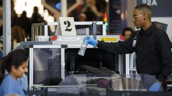An agent removes a water bottle as baggage is screened at a Transportation Security Administration (TSA) checkpoint at Los Angeles International Airport (LAX) in Los Angeles, California, U.S., on Thursday, Oct. 25, 2018. A new LAX policy will allow travelers to possess a small amount of marijuana inside the airport, and on planes, if the traveler is flying to a state where weed is legal. Photographer: Patrick T. Fallon/Bloomberg via Getty Images