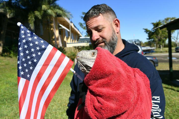 A gentle soul cares for a patriotic iguana.