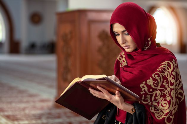 Young Muslim woman praying in mosque with