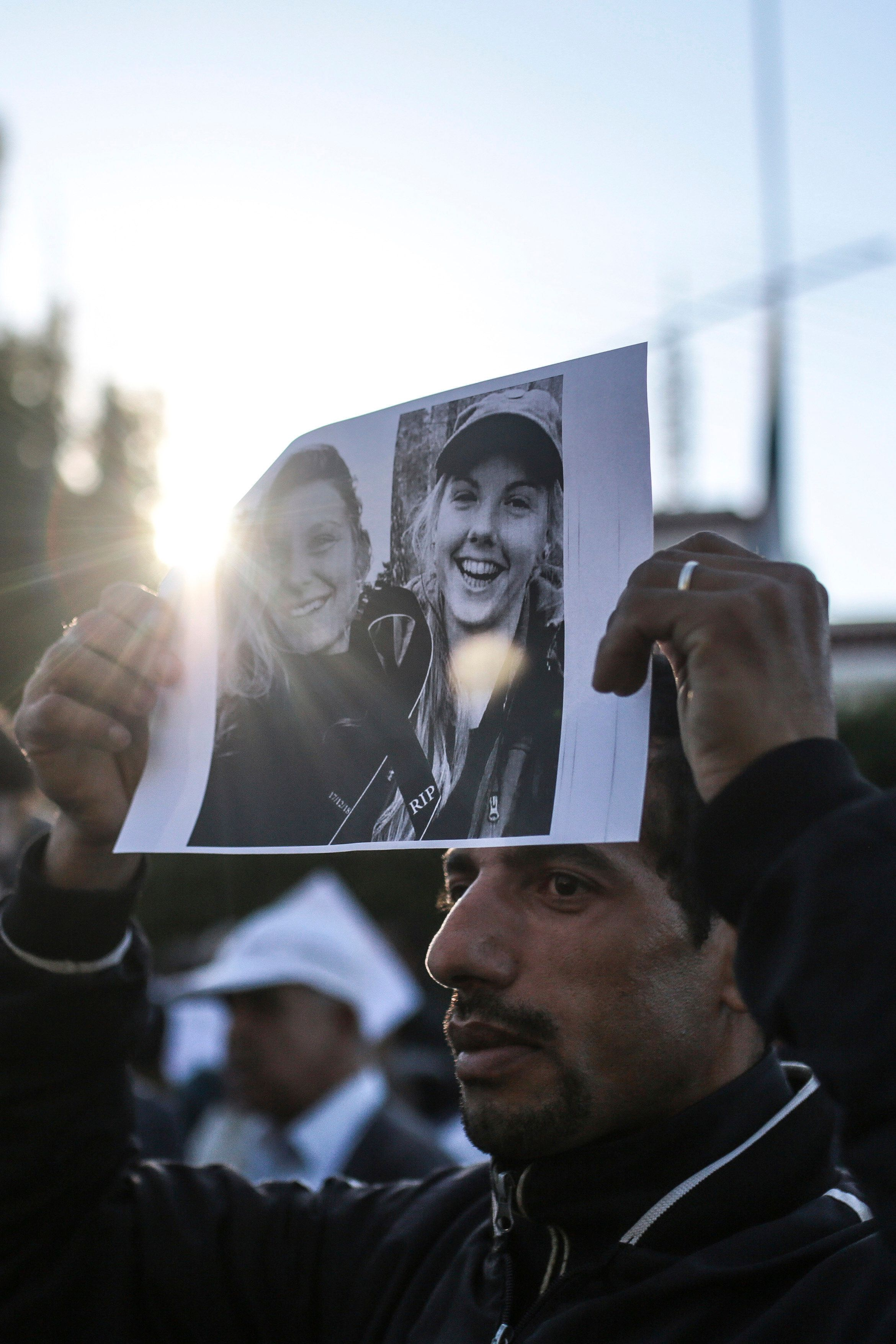A man carries the picture of 28-year-old Norwegian Maren Ueland and 24-year-old Danish Louisa Vesterager Jespersen, during a candlelight vigil outside the Norwegian embassy in Rabat for the two Scandinavian university students who were killed in a terrorist attack in a remote area of the Atlas Mountains, Morocco, Saturday, Dec. 22, 2018. Moroccans gathered Saturday in front of the Norwegian and Danish embassies in Rabat in a candlelight vigil to honor two Scandinavian university students killed in a terrorist attack in the Atlas Mountains. (AP Photo/Mosa'ab Elshamy)