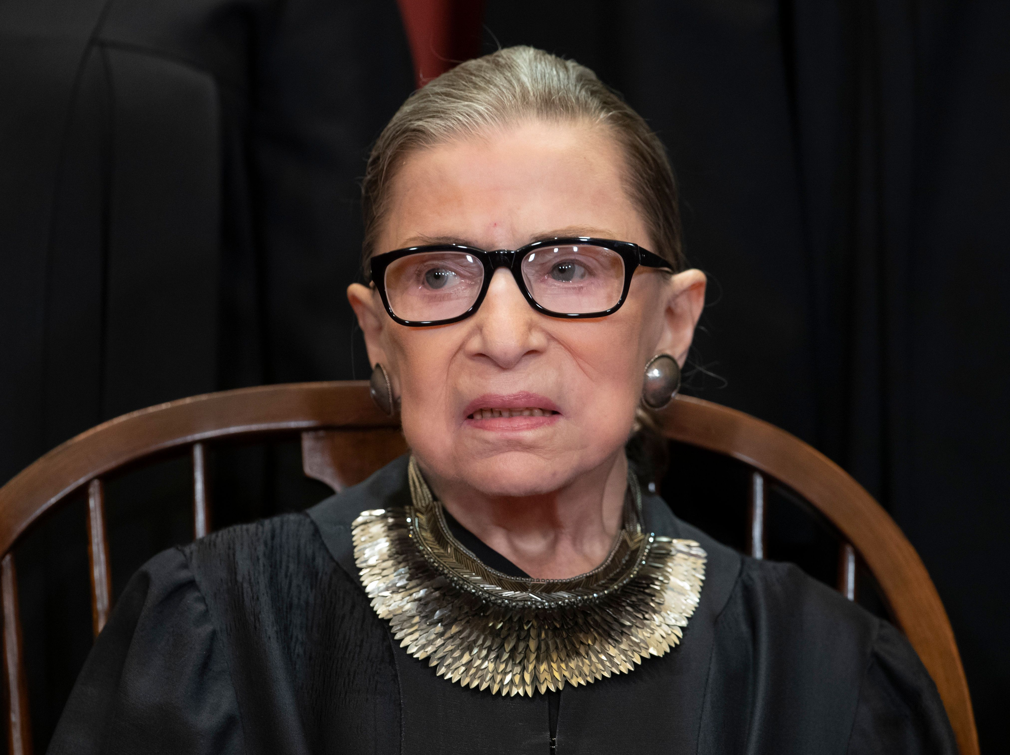 FILE - In this Nov. 30, 2018 file photo, Associate Justice Ruth Bader Ginsburg, nominated by President Bill Clinton, sits with fellow Supreme Court justices for a group portrait at the Supreme Court Building in Washington, Friday. The Supreme Court says Justice Ruth Bader Ginsburg has undergone surgery to remove two malignant growths from her left lung. It is Ginsburg's third bout with cancer since joining the court in 1993. (AP Photo/J. Scott Applewhite)