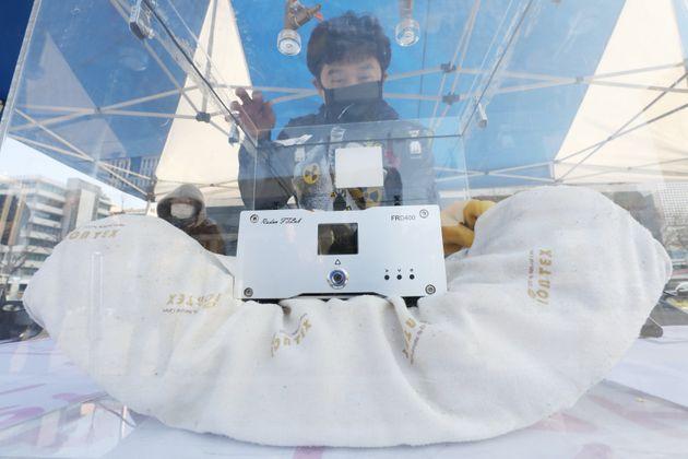 환경보건시민센터 활동가가 11월 26일 오전 서울 광화문광장에서 시중 제품 중 방사선 라돈이 나오는 제품들을 모아 측정 시연을 하고