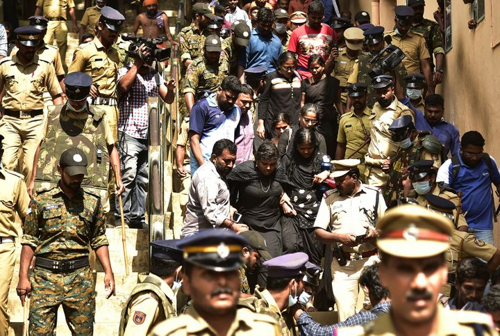 Cops escort women activist from a 'Manithi' NGO as they return back after being surrounded by Hindu activist to stop their attempt to reach Sabarimala Ayyapa temple, in Pamba in Kerala, on December 23, 2018.