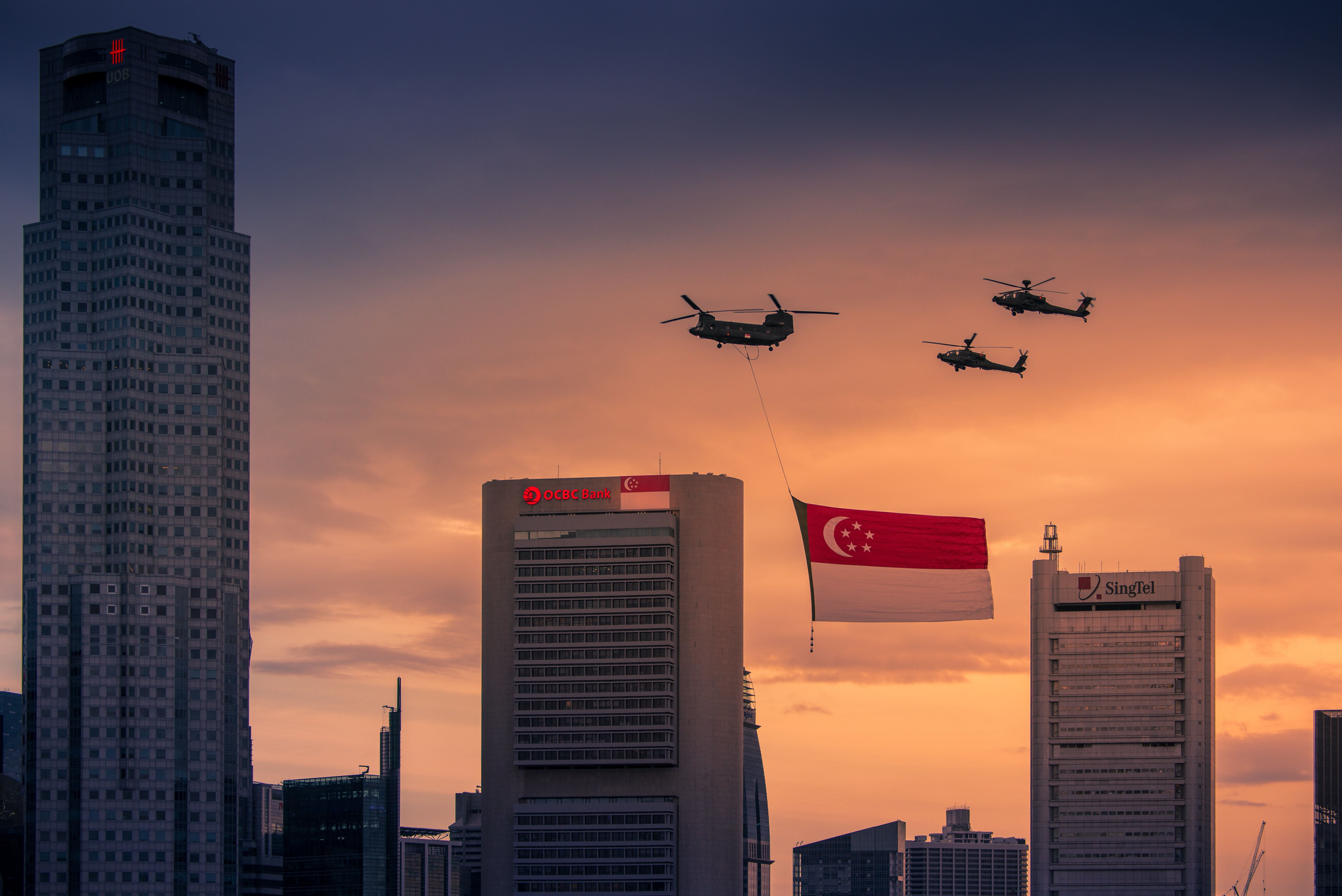 Chinook carrying the state flag, followed by 2 Apaches AH64D during the National Day Parade Marina Bay on August 9, 2014 in Singapore. It is Singapore's 49th birthday with a parade theme of 'Our People, Our Home'.