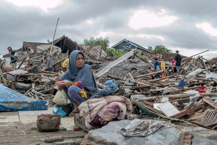 Everything is gone: A tsunami survivor sits on debris from her house in Sumur, Indonesia.