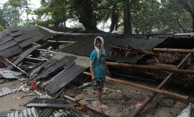 Un homme devant les débris de sa maison à