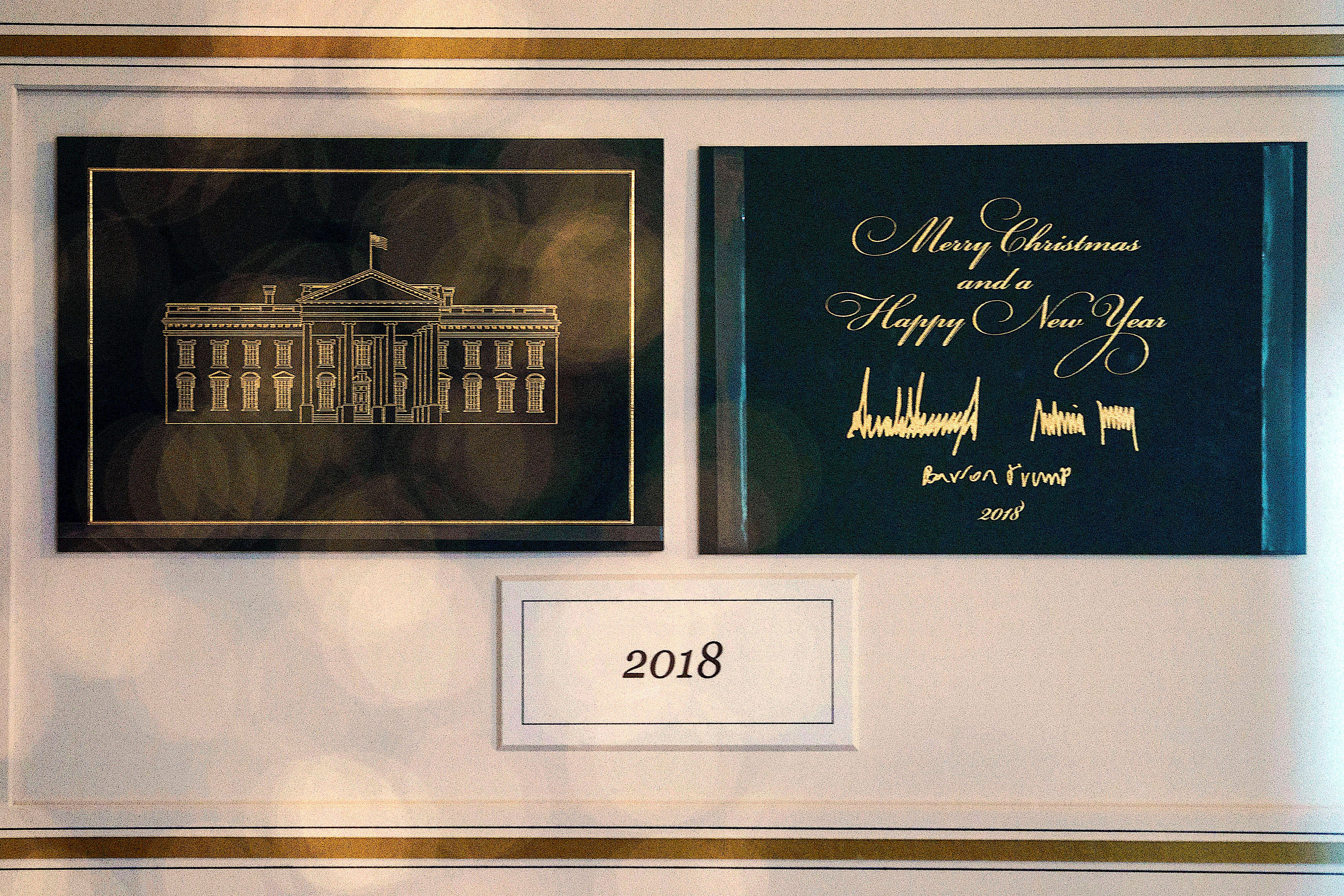"The First Family's holiday card is seen behind glass in Booksellers during the 2018 Christmas preview at the White House in Washington, Monday, Nov. 26, 2018. Christmas has arrived at the White House for 2018 as first lady Melania Trump unveiled the holiday decor. She designed the decor, which features a theme of ""American Treasures."" (AP Photo/Carolyn Kaster)"