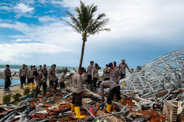 Police officers search for victims among rubble of a destroyed beach front hotel, which was hit by a...