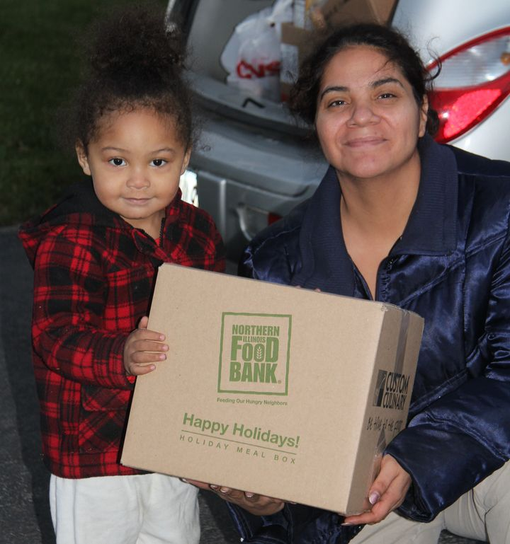 Veronica and her 2-year-old daughter receive a holiday meal box at Open Arms Mission Food Pantry in Antioch, Illinois, in 201