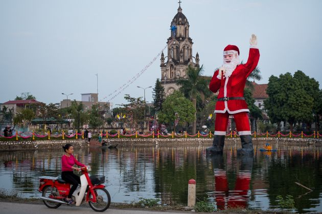 A giant, floating Santa Claus stands in a lake in front of Phu My Cathedral outside Hanoi,