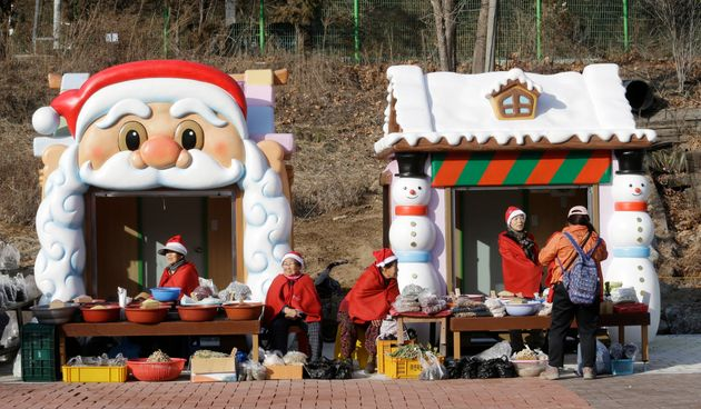 People wearing Santa Claus outfits to celebrate Christmas sell products at the Santa Village near the...