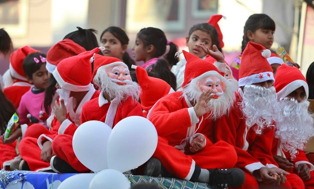 Children dressed as Santa Claus participate in a procession in Jammu,