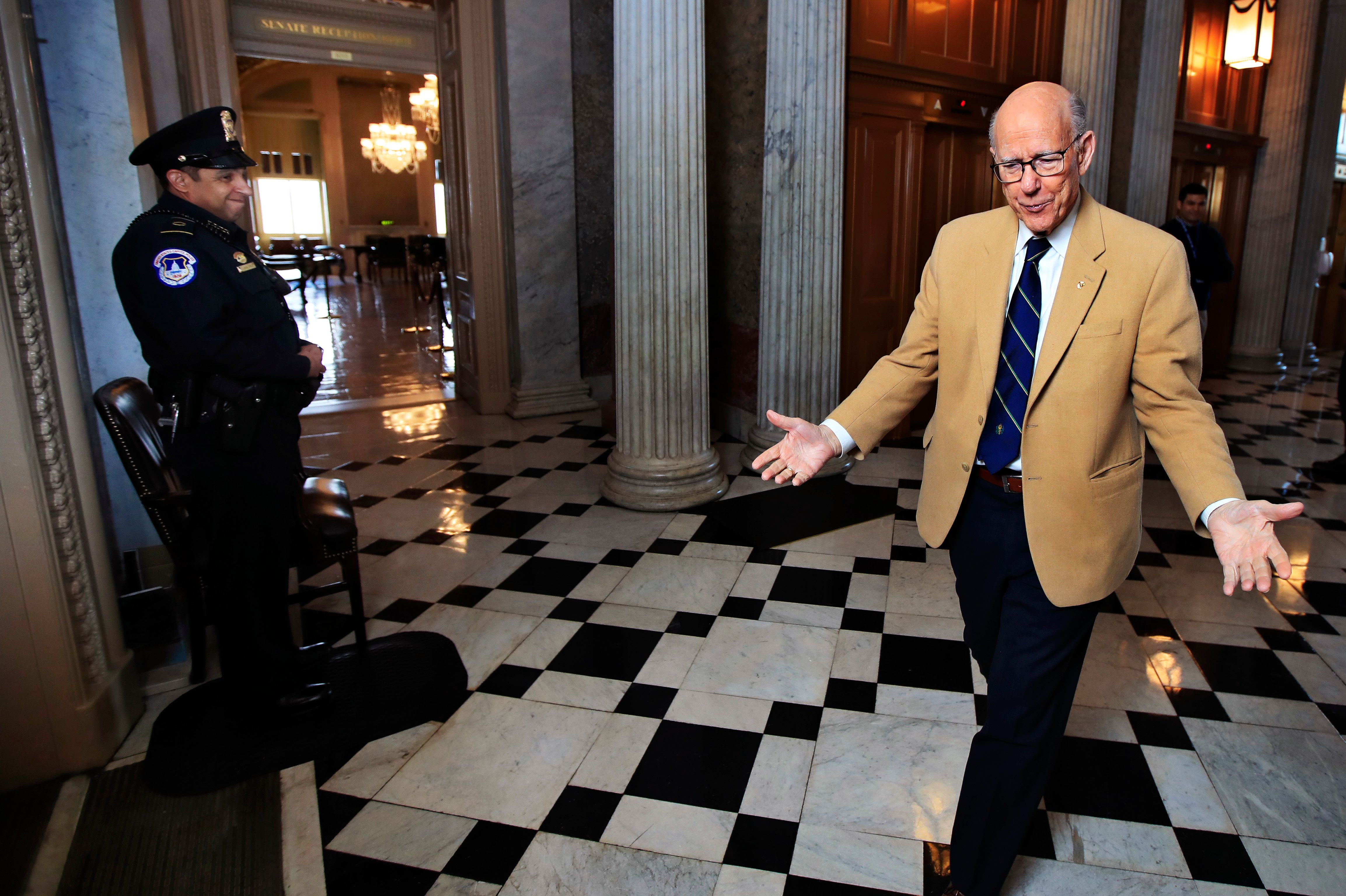 Sen. Pat Roberts, R-Kan., right, greets U.S. Capitol Police Officer John Cruz and Senate floor doorkeeper Gwen Barnhardt as he walks the empty hallways of Capitol Hill in Washington, Monday, Dec. 24, 2018. Roberts was on Capitol Hill for a pro forma session, a brief meeting of the Senate only a few minutes in duration. Both sides in the long-running fight over funding President Donald Trump's U.S.-Mexico border wall appear to have moved toward each other, but a shutdown of one-fourth of the federal government entered Christmas without a clear resolution in sight. (AP Photo/Manuel Balce Ceneta)