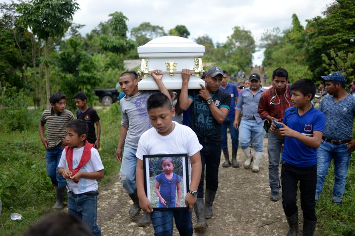 A boy carries a picture of Guatemalan 7-year-old Jakelin Caal, who died in a Texas hospital two days after being taken into c