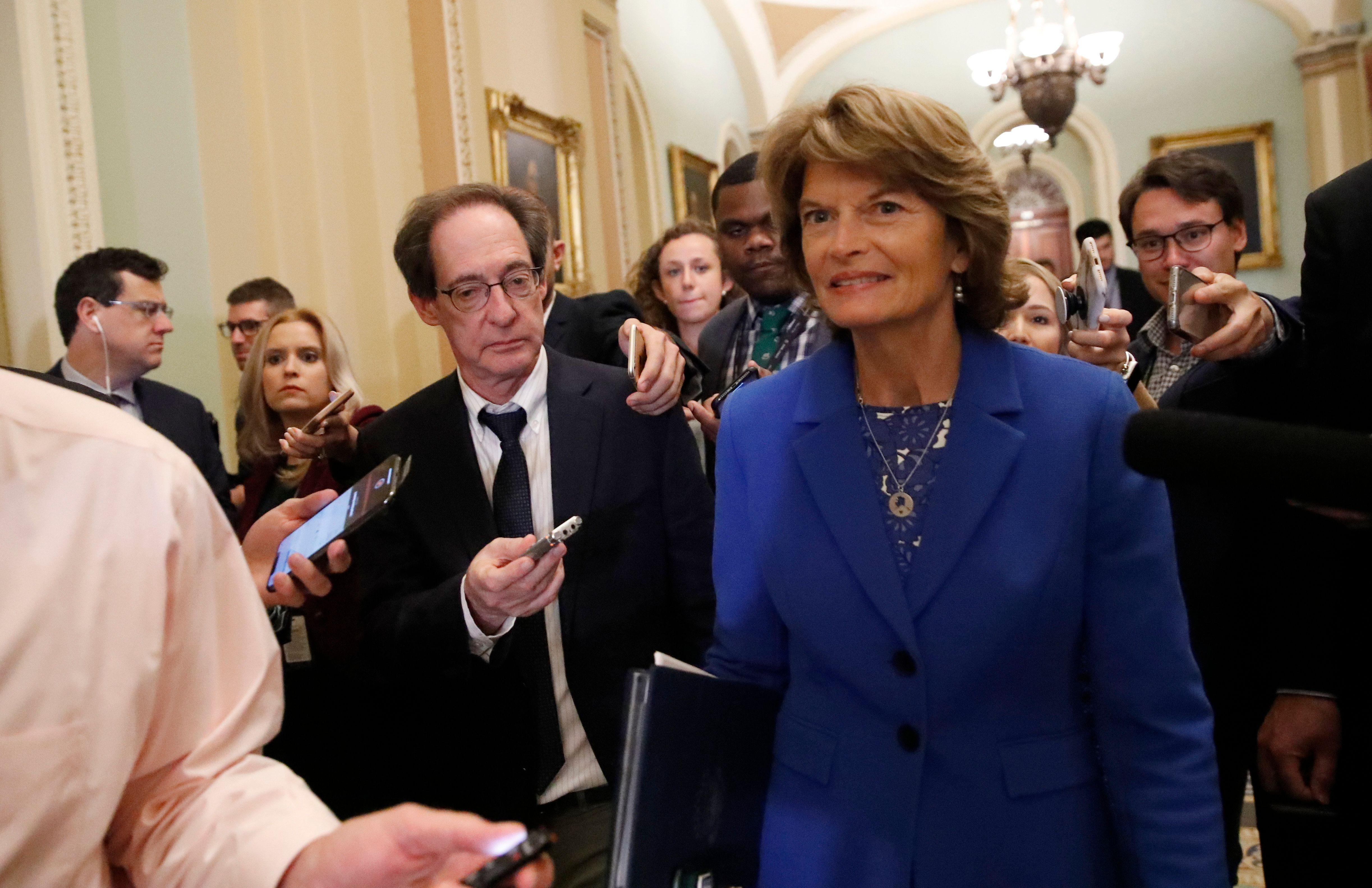 Sen. Lisa Murkowski, R-Alaska, right, walks with journalists as she departs the Republican policy luncheon, on Capitol Hill, Tuesday, Sept. 25, 2018 in Washington. (AP Photo/Alex Brandon)