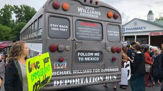 "A Georgia gubernatorial candidate touring the state in a ""deportation bus"" is greeted with protests by immigrants and other residents in Clarkston, Ga., Wednesday, May 16, 2018. State Sen. Michael Williams, who trails in public polling, has received condemnation for the move just days before voters make their choice in the May 22 primary elections. (AP Photo/Benjamin Nadler)"