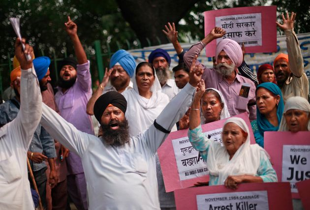 Sikhs hold placards as they shout slogans during a protest to demand justice for victims of the 1984...