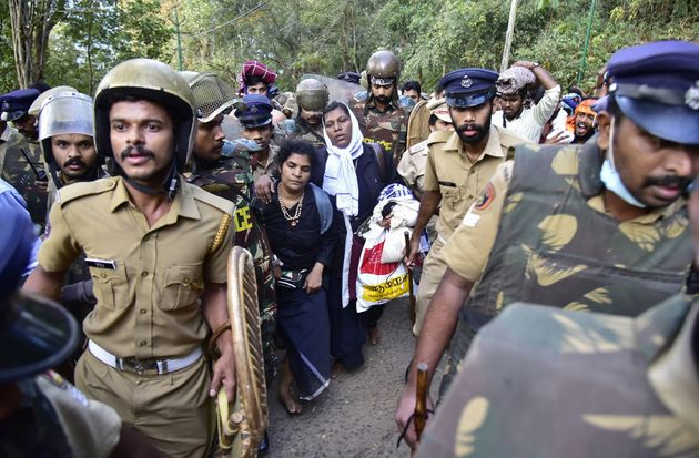 Police escort Kanaga Durga and Bindu after their group of women was stopped by protesters during an effort...