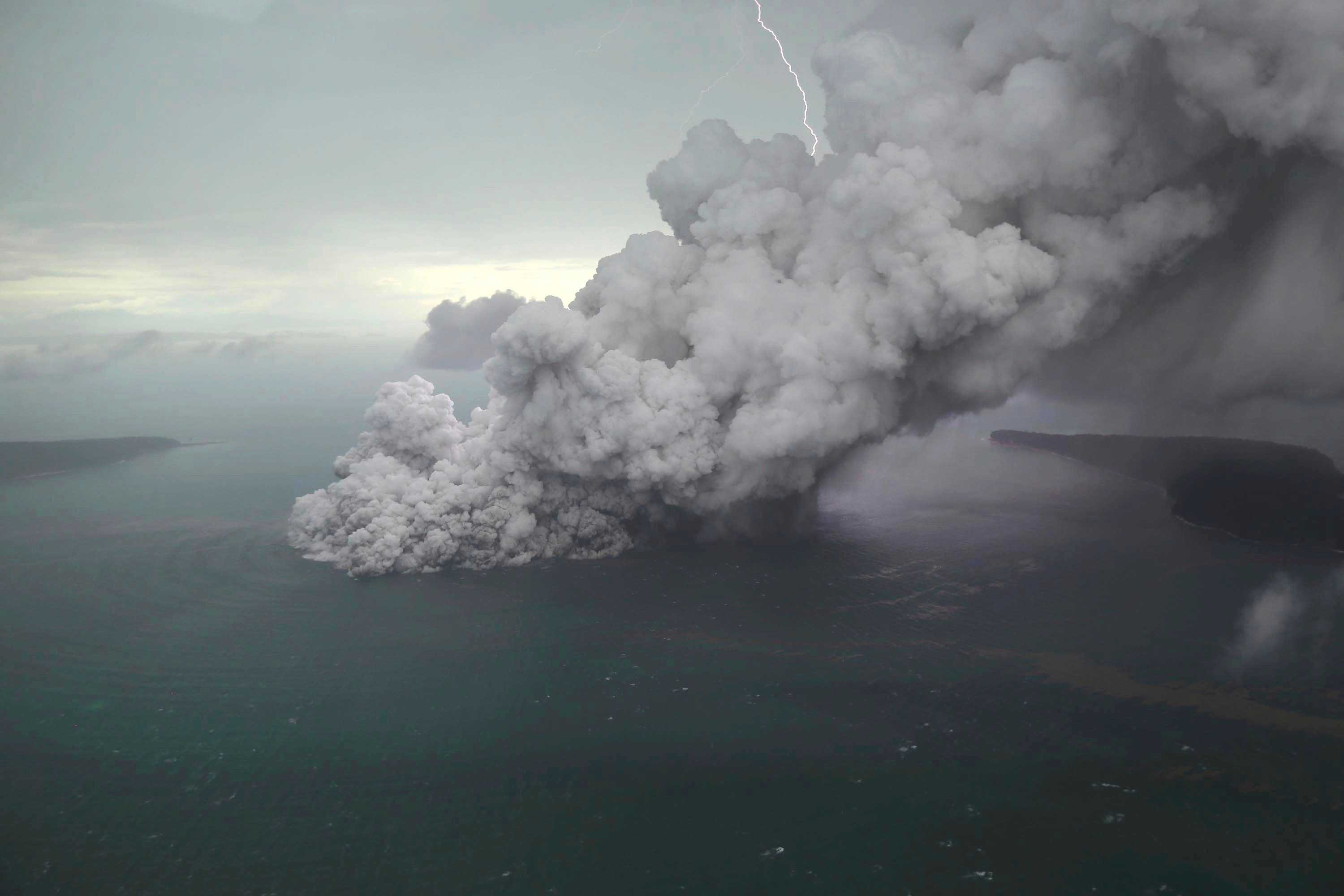 This aerial shot taken on Sunday, Dec. 23, 2018, shows volcanic material spew from the crater of Mount Anak Krakatau as it erupts on Java Strait, Indonesia. Doctors worked to save injured victims while hundreds of military and volunteers scoured debris-strewn beaches in search of survivors Monday, Dec. 24, 2018, after a deadly tsunami that followed an eruption and apparent landslide the volcano, one of the world's most infamous volcanic islands, gushed ashore without warning on Indonesian islands, killing hundreds of people on a busy holiday weekend. (Nurul Hidayat/Bisnis Indonesia via AP)