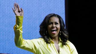 "Former first lady Michelle Obama, left, waves to a crowd as Sarah Jessica Parker watches during an appearance for her book, ""Becoming: An Intimate Conversation with Michelle Obama"" at Barclays Center Wednesday, Dec. 19, 2018, in New York. (AP Photo/Frank Franklin II)"