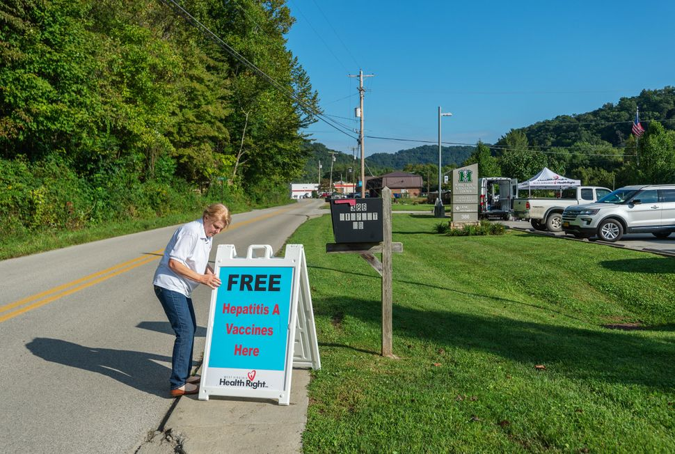 Brenda Parker, who works for West Virginia Health Right, sets up a sign advertising free hepatitis A vaccines as part of a mo