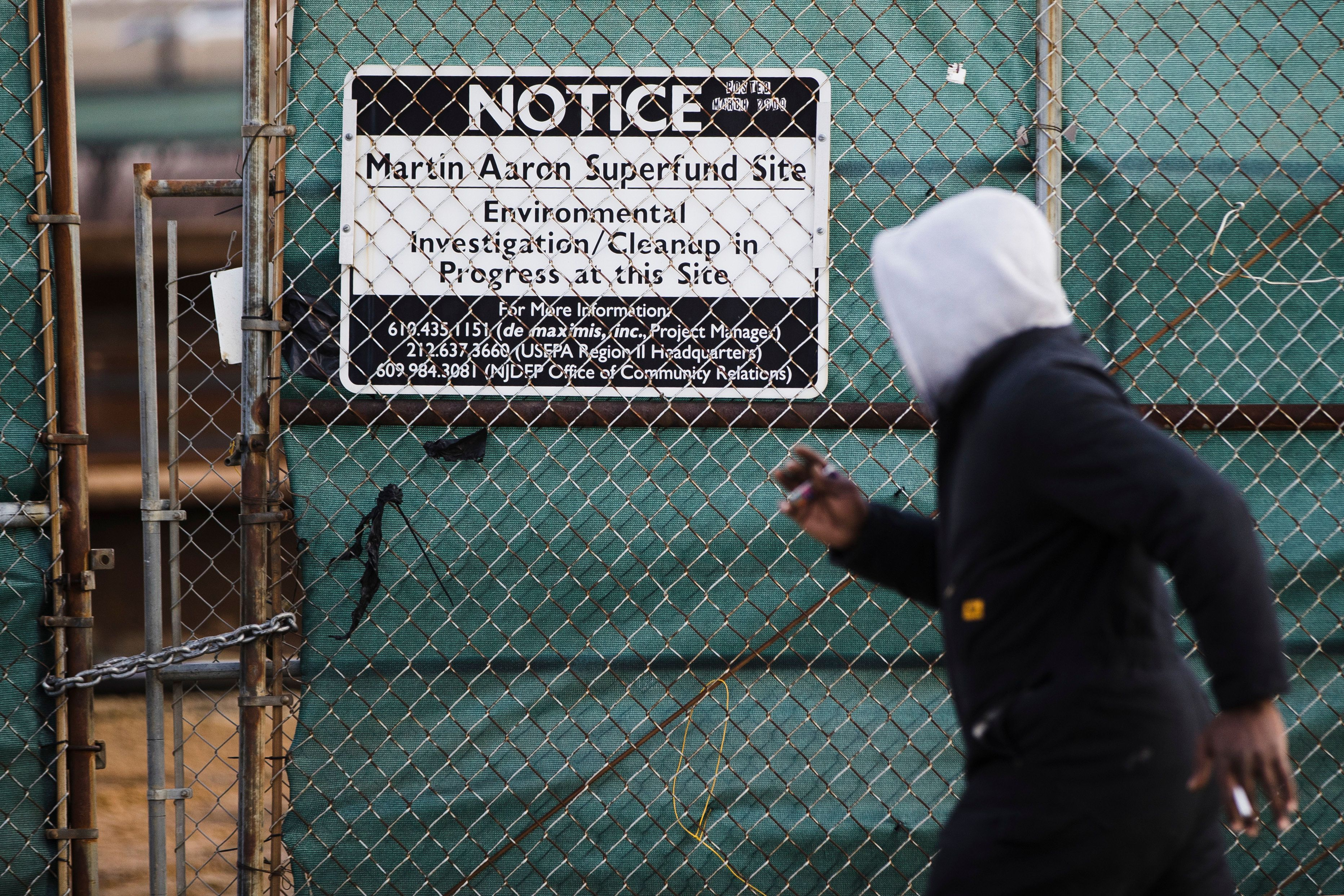 FILE - In this Dec. 11, 2017, file photo, a man walks past a notice for the Martin Aaron Inc. Superfund site in Camden, N.J. A lawyer tapped to lead a task force at the Environmental Protection Agency overseeing cleanups at the nation's most polluted places until recently worked for a top chemical and plastics manufacturer with a troubled legacy of creating some of those toxic sites. (AP Photo/Matt Rourke, File)
