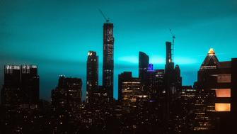 Buildings stand as the night sky is illuminated by blue light in New York, U.S., on Thursday, Dec. 27, 2018. The New York Police Department is investigating a transformer explosion at Astoria East & North Queens from a Consolidated Edison Inc. power plant, the NYPD 114th Precinct said in a tweet. Photographer: Jeenah Moon/Bloomberg via Getty Images
