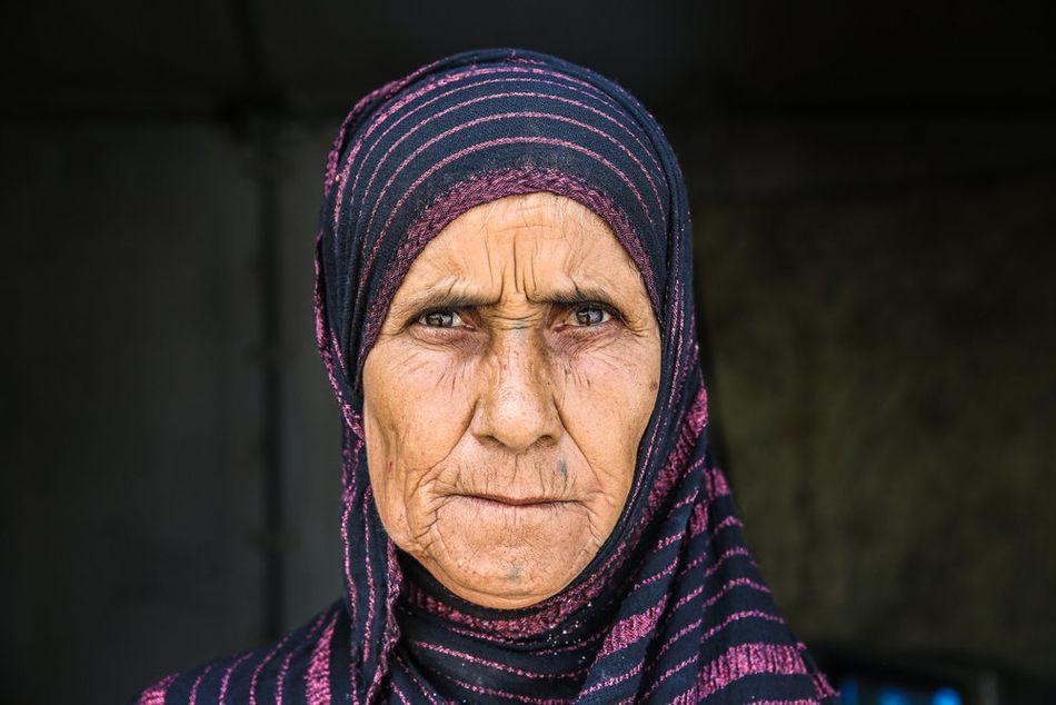 Η Ρασμίγια, 63 ετών, που μεγάλωσε επτά γιους και τέσσερις κόρες, τώρα ζει μόνη στον καταυλισμό εσωτερικά εκτοπισμένων του Αμριγιάτ Αλ-Φαλούτζα. Η ιστορία της Ρασμίγια είναι αντιπροσωπευτική των πολλών επιπέδων βίας και απώλειας που έχουν υποστεί πολλοί άνθρωποι στο Ιράκ τα τελευταία χρόνια. Έχασε τέσσερις από τους επτά γιους της στον βομβαρδισμό της Φαλούτζα, όπου ζούσαν, το 2004. Ένας άλλος γιος της είναι στη φυλακή από το 2006 με την κατηγορία ότι συνεργαζόταν με αντάρτες, ενώ ένας άλλος έχει απαχθεί από ομάδα ενόπλων και δεν έχει δώσει σημεία ζωής από τότε. Οι έβδομος γιος και οι κόρες της ζουν στη Βαγδάτη, όμως δεν μπορεί να φύγει για να τους δει, καθώς υπάρχουν σημεία ελέγχου γύρω από τον καταυλισμό. (Οκτώβριος 2018).