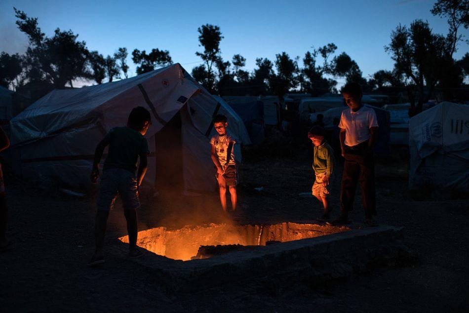 Παιδιά γύρω από τη φωτιά στον καταυλισμό της Μόριας. Χιλιάδες άνθρωποι που αναζητούν ασφάλεια από χώρες όπως η Συρία, το Αφγανιστάν, το Ιράκ, το Σουδάν και το Κονγκό συνεχίζουν να διακινδυνεύουν τη ζωή τους για να φτάσουν στην Ευρώπη. Όσοι προσπαθούν να έρθουν μέσω της Τουρκίας και του Αιγαίου εγκλωβίζονται επ' αόριστον στα ελληνικά νησιά στο πλαίσιο της συμφωνίας ΕΕ-Τουρκίας και της πολιτικής αποτροπής και περιορισμού που υπαγορεύεται από αυτή. (Ιούλιος 2018)