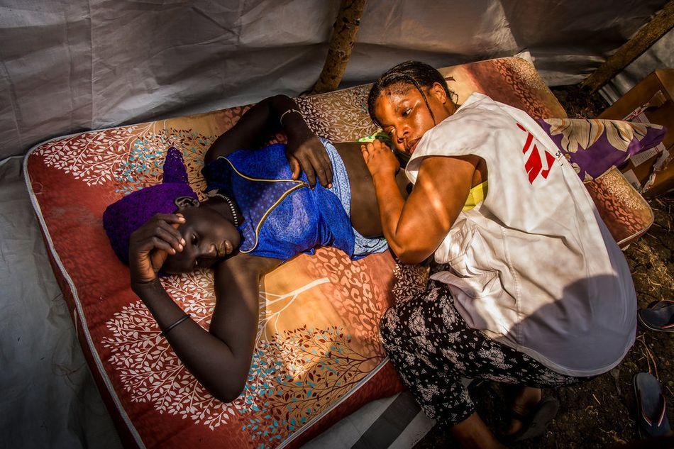 Η νοσηλεύτρια και μαία Φουράχα Μπαζικάνια εξετάζει μια νεαρή έγκυο σε έναν από τους δύο χώρους εξέτασης μιας κινητής μονάδας σε χωριό. (Δεκέμβριος 2017)