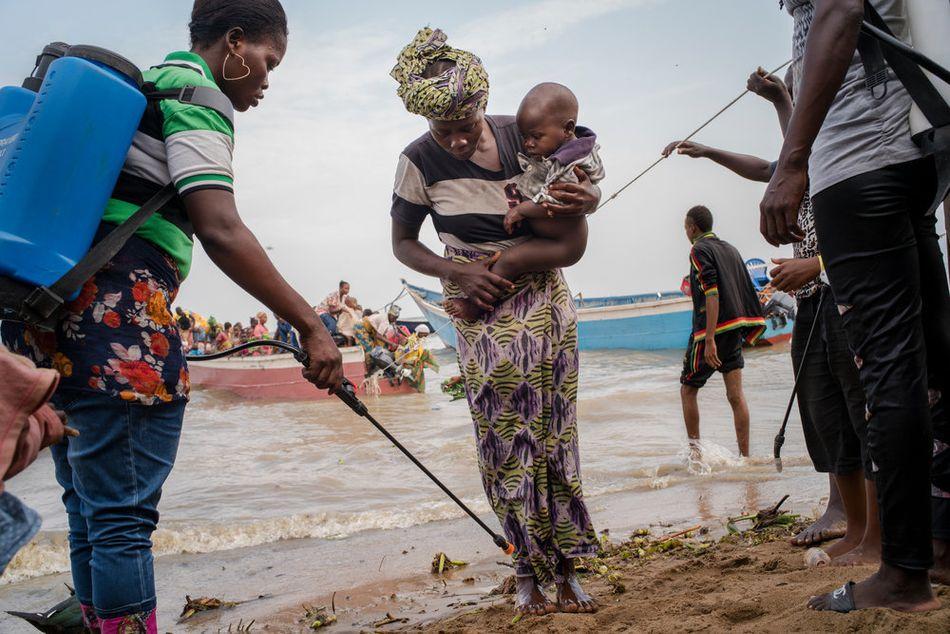 Εργαζόμενοι απολύμανσης ψεκάζουν τα χέρια και τα πόδια των Κονγκολέζων προσφύγων που φτάνουν στις όχθες της λίμνης Άλμπερτ, σε μια περιοχή όπου η χολέρα είναι ενδημική. Περίπου 60.000 πρόσφυγες έφτασαν στην Ουγκάντα με βάρκες από τον Δεκέμβριο του 2017 έως τον Μάρτιο του 2018, για να γλιτώσουν από τις συγκρούσεις στην επαρχία Ιτούρι της Λαϊκής Δημοκρατίας του Κονγκό. (Μάρτιος 2018)