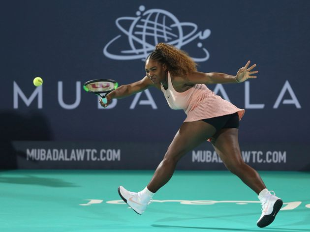Serena Williams returns the ball to her sister Venus during a match at the opening day of the Mubadala...