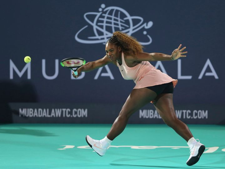 Serena Williams returns the ball to her sister Venus during a match at the opening day of the Mubadala World Tennis Champions