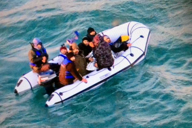 Migrants seen onboard a boat near to the French port of Calais in the English Channel earlier this