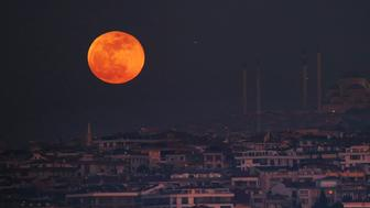 A super blue blood moon rises over Istanbul, behind the Camlica Mosque, the largest mosque in Asia Minor, Wednesday, Jan. 31, 2018. It's the first time in 35 years a blue moon has synced up with a supermoon and a total lunar eclipse, or blood moon because of its red hue, all rolled into one celestial phenomenon. (AP Photo/Emrah Gurel)