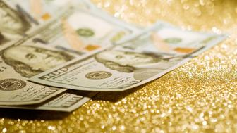 The dollars banknotes on gold glitter background represent the concept of wealth and investment success.