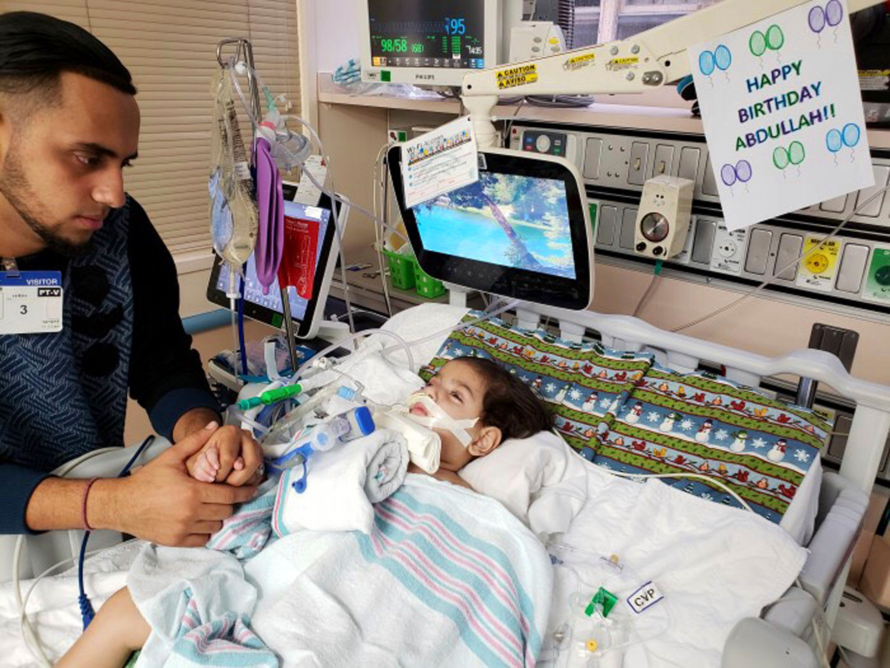 This recent but undated photo, released Monday, Dec. 17, 2018 by the Council on American-Islamic Relations in Sacramento, Calif., shows Ali Hassan with his dying 2-year-old son Abdullah in a Sacramento hospital. The boy's Yemeni mother, blocked by the Trump administration's travel ban, has won her fight for a waiver that would allow her to travel to California to see her son. Basim Elkarra of the Council on American-Islamic Relations in Sacramento said Shaima Swileh was granted a visa Tuesday and will be flying to San Francisco on Wednesday, Dec.19. (Council on American-Islamic Relations via AP)