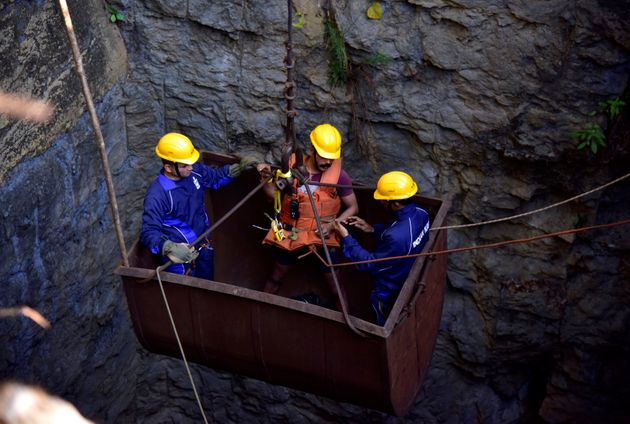 Divers use a pulley to enter a coal mine that collapsed in Ksan, in Meghalaya,, December 29,