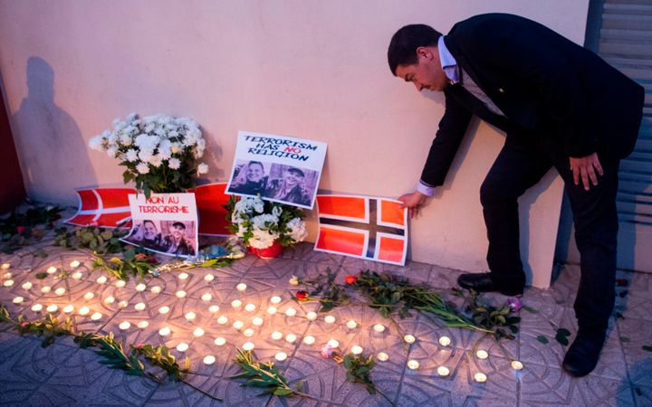 A Moroccan man places a Norwegian flag next to flowers and the portraits of murdered Danish student Louisa Vesterager Jespers