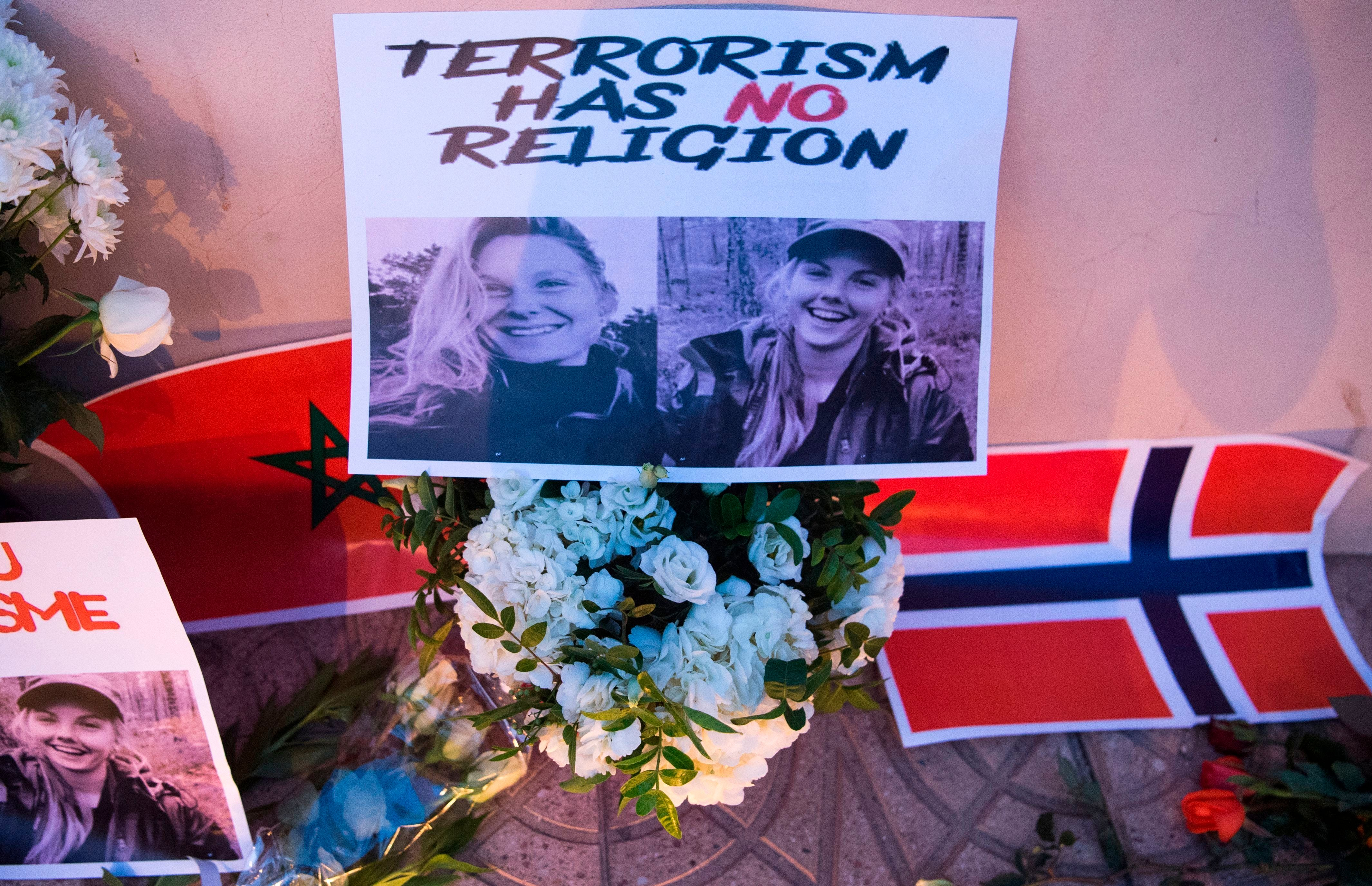 This picture taken on December 21, 2018 shows a combo photo murdered Danish student Louisa Vesterager Jespersen (L) and Nowegian Maren Ueland placed on top of flowers and between the flags of Morocco an Norway as Moroccans pay tribute to the Scandinavian victims. - The bodies of the 24-year-old Danish student 28-year-old Norwegian were found on December 17, after the two friends had pitched their tent at an isolated mountain site two hours' walk from the tourist village of Imlil. (Photo by FADEL SENNA / AFP)        (Photo credit should read FADEL SENNA/AFP/Getty Images)
