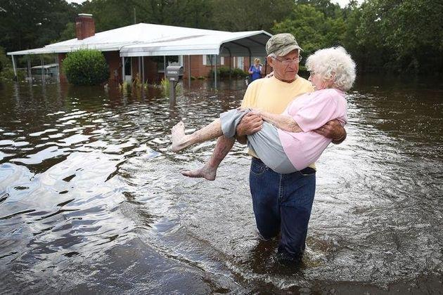 Ένας άνδρας μεταφέρει στα χέρια του τη συζυγό του, αντιμέτωπος με τα νερά της καταστροφής