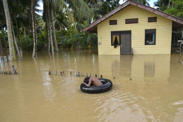 Στην επαρχία Aceh, ένα αγόρι βρίσκεται μόνος με το σωσίβιό του στα απόνερα της καταστροφής