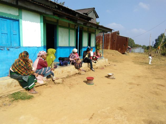 Melambok and Dimonme's mother, Jostina Dkhar (in the green shawl) sits on the verandah of the family's