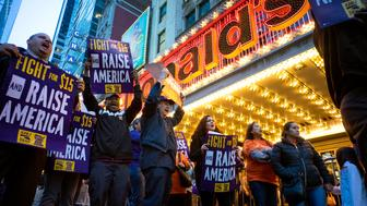 FILE - In this Wednesday, April 15, 2015, file photo, protestors pause near a McDonald's restaurant in Times Square during a rally and march in New York, as participants, fast food workers and union members call for a $15 minimum wage. Labor organizers say they're planning another day of strikes and protests exclusively targeting McDonald's stores in dozens of cities on April 14, 2016, following similar demonstrations outside a variety of fast-food restaurants a year ago. (AP Photo/Craig Ruttle, File)