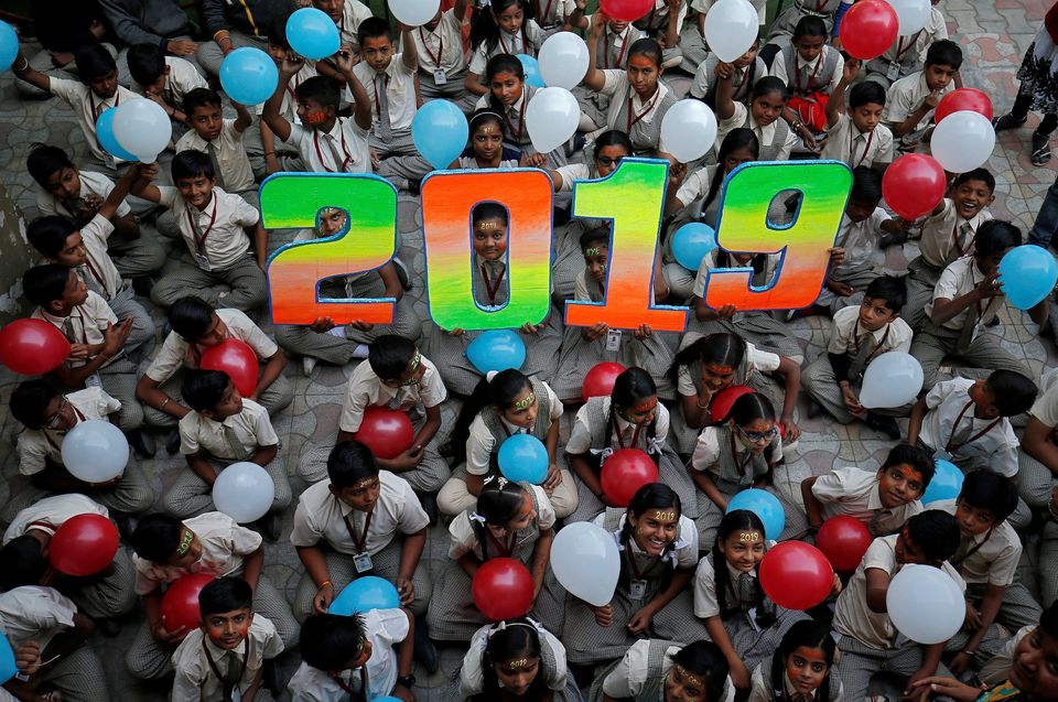 Schoolchildren in Ahmedabad, India, pose as part of celebrations to welcome the new